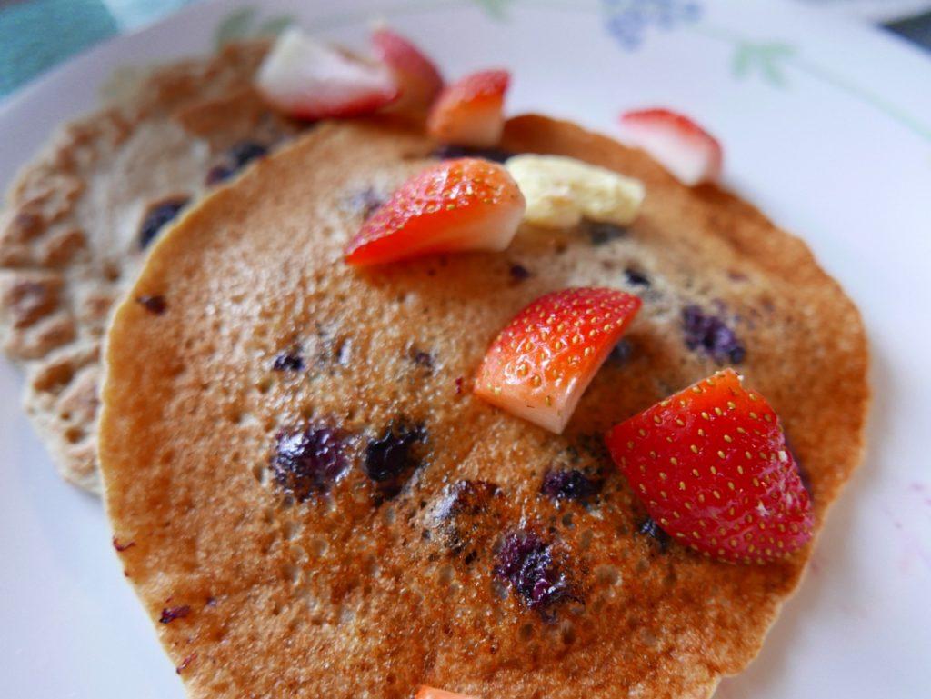 blueberry pancakes sprinkled wth sliced strawberries
